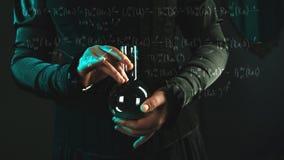 La femme est une scientifique de recherches tenant un flacon avec le mat?riel Concept de recherche scientifique et histoire de la photos stock