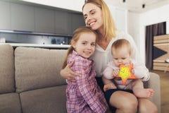 La femme est venue à la maison et étreint ses enfants La fille et le bébé sont heureux au sujet du retour de la maman Photos stock
