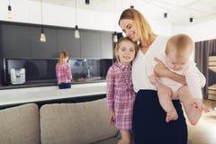 La femme est venue à la maison et étreint ses enfants La fille et le bébé sont heureux au sujet du retour de la maman Photo stock