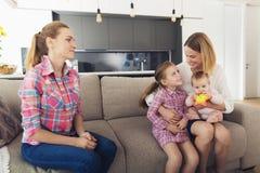 La femme est venue à la maison et étreint ses enfants Une babysitter s'assied à côté de eux Photos stock