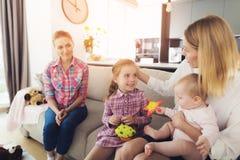 La femme est venue à la maison et étreint ses enfants Une babysitter s'assied à côté de eux Photos libres de droits