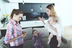 La femme est venue à la maison et châtie l'infirmière, qui n'a pas bien suivi les enfants Photo libre de droits