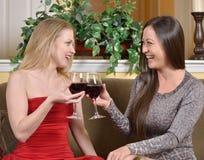 La femme et l'ami biracial renversants grillent avec du vin Photographie stock libre de droits