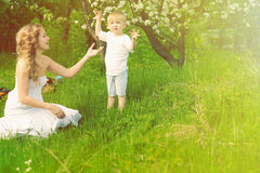 La femme et l'enfant heureux pendant le ressort de floraison font du jardinage photos stock