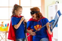 La femme et l'enfant heureux se préparent au nettoyage de pièce Mère et sa fille d'enfant jouant ensemble Famille dans des costum Image libre de droits