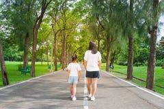 La femme et l'enfant marchant sur le sentier piéton et le passage couvert en parc public et bonheur se sentant et apprécient photo stock