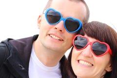 La femme et l'homme avec des verres ont formé le coeur, heure d'été Photographie stock libre de droits