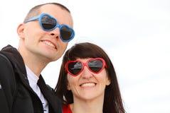 La femme et l'homme avec des verres ont formé le coeur, heure d'été Photos stock