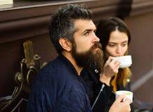 La femme et l'homme avec les visages réfléchis ont la date au café Photographie stock libre de droits
