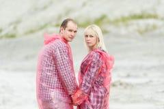 La femme et l'homme dans des imperméables protecteurs Image libre de droits