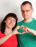 La femme et l'homme de sourire avec des mains au coeur forment images stock