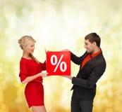 La femme et l'homme de sourire avec la vente rouge de pour cent signent Photographie stock