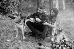La femme et l'homme des vacances, apprécient la nature Couplez le jeu avec le chien de berger allemand près du feu, fond de forêt Photo libre de droits