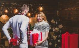 La femme et l'homme donnent des cadeaux de Noël entre eux Beaux couples heureux photos libres de droits