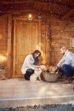 La femme et l'homme préparent le bois de chauffage sur la montagne Image libre de droits