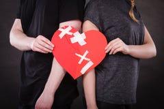 La femme et l'homme remet tient le coeur brisé Photos stock
