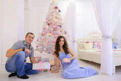 La femme et l'homme remettent à des cadeaux de Noël sa moitié dans le bedro spacieux Photo stock