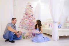 La femme et l'homme remettent à des cadeaux de Noël sa moitié dans le bedro spacieux Photographie stock libre de droits