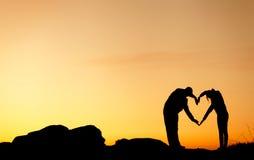 La femme et l'homme remettent la silhouette au-dessus du ciel au fond de coucher du soleil Photographie stock libre de droits