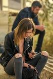 La femme et l'homme s'asseyent avec le téléphone portable Photographie stock libre de droits