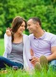 La femme et l'homme s'asseyent sur l'herbe en parc et mangent le raisin Photo libre de droits