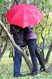 La femme et l'homme se cachent derrière le parapluie rouge dans le stationnement Photos stock