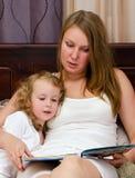 La femme et la petite fille ont affiché un livre Image stock