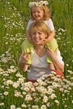 La femme et la petite fille sur la marguerite mettent en place photographie stock libre de droits