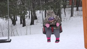 La femme et le bébé de mère balancent sur le terrain de jeu d'hiver Tempête de neige de neige 4K clips vidéos