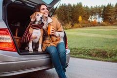 La femme et le chien avec des châles s'assied ensemble dans le tronc de voiture l'automne Photographie stock libre de droits