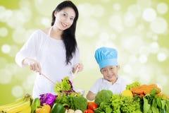 La femme et le garçon attirants font la salade Image libre de droits