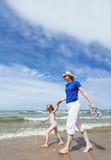 La femme et le petit enfant marchant en mer échouent Photographie stock