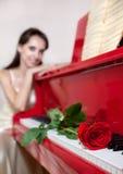 La femme et le rouge se sont levés sur le piano rouge Image libre de droits