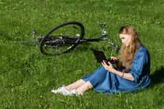 La femme et le vintage vont à vélo, ordinateur portable, pelouse verte, été Fille rouge de cheveux s'asseyant sur l'herbe en deho Photographie stock libre de droits