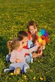 La femme et les gosses jouant avec un moulin à vent jouent Photos libres de droits