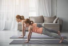 La femme et sa fille faisant la planche s'exercent à la maison Photos stock