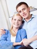 La femme et son ami s'étreignent sur le sofa Image stock
