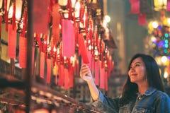 La femme a eu plaisir ? regarder les lampes rouges et les souhaits dans le temple chinois photographie stock