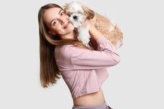 La femme européenne positive avec de longs cheveux embrasse son animal familier préféré avec la fourrure pelucheuse, habillée dan images stock