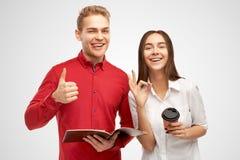 La femme européenne sûre heureuse et le bel homme avec le large sourire, coiffure élégante, montre le geste d'ok image stock