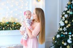 La femme européenne tenant l'enfant féminin dans des bras et la position près a décoré la cheminée et l'arbre de Noël image stock