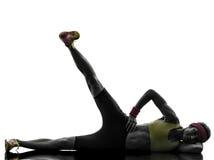 La femme exerçant des pieds de séance d'entraînement de forme physique lèvent la silhouette Image libre de droits