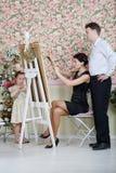 La femme explique son plan à l'artiste et la petite fille se tient Photos libres de droits