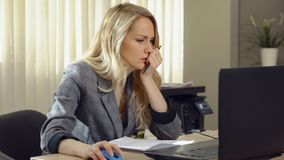 La femme fâchée d'affaires dans le costume travaille à l'ordinateur dans le bureau photographie stock