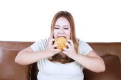 La femme fâchée mange un hamburger sur le studio images libres de droits