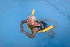 La femme féminine supérieure se tient dessus sur un dispositif de flottaison sur une piscine pour apprendre comment nager image stock