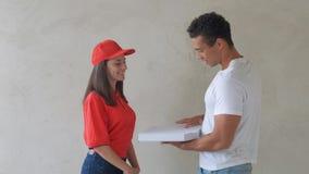 La femme facile à vivre de la livraison de pizza tient des boîtes à nourriture dans l'uniforme rouge banque de vidéos