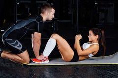 La femme faisant des craquements abdominaux pressent l'exercice sur le tapis avec son entraîneur de mâle de sports image libre de droits