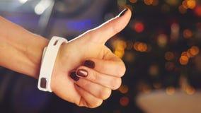 La femme faisant des gestes sur un dispositif portable d'ordinateur de smartwatch et fait le pouce à la fin sur Noël brouillé de  Image libre de droits