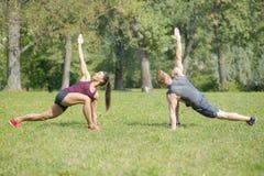 La femme faisant l'étirage s'exerce avec l'entraîneur personnel en parc Photographie stock libre de droits